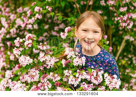 Outdoor portrait of a cute little girl of 8-9 years old, playing with spring flowers