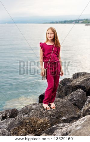 Fashion stylish portrait of pretty preteen girl of 8-9 years old, wearing maroon jumpsuit, posing by the lake