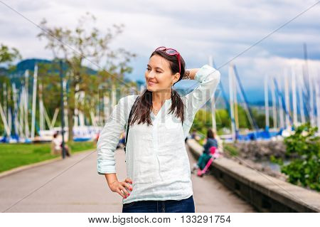 Young brunette woman with backpack, walking in the park