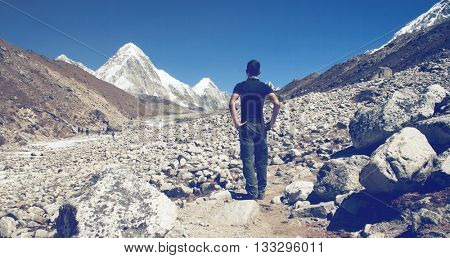 Man standing surveying a glacier in Nepal with his back to the camera as he looks towards the snow covered Himalayas