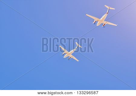 Two small aircrafts flying together in a blue sky