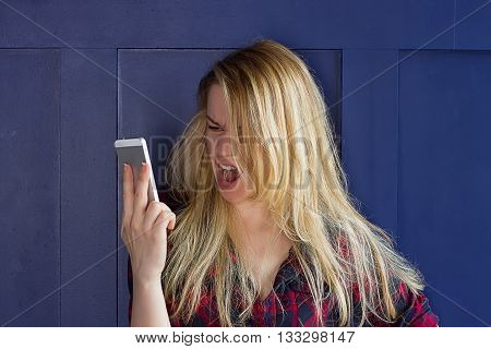 Portrait angry young woman screaming on mobile phone. Negative emotions feelings