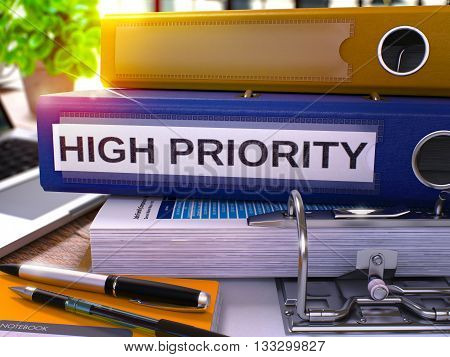 High Priority - Blue Office Folder on Background of Working Table with Stationery and Laptop. High Priority Business Concept on Blurred Background. High Priority Toned Image. 3D.