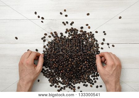 Close-up hands of man on a wooden surface with spreaded coffee beans. Grain selection. Top view composition. Workplace coffee maker or sorter. Art composition. Concept. Coffee house. Coffee break.
