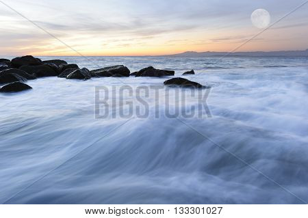 Ocean seascape is an image of ocean waves flowing through rocks as the moon rises over the horizon .