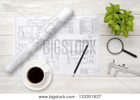 Drawing sketches, magnifier, cup of coffee and houseplant are on wooden surface. Top view compositin. Workplace of architect or constructor. Engineering work. Construction and architecture. Architect drawing. Exact calculation. Office workplace. Increase