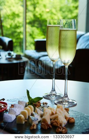 two glasses of champagne with a tray of cheese