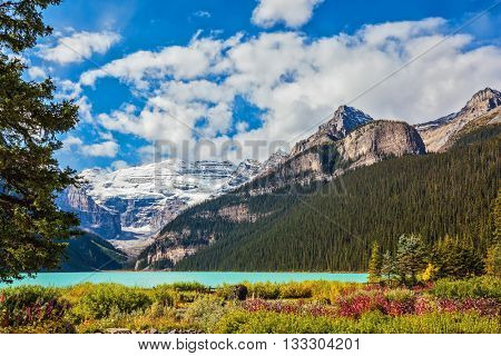 The picturesque promenade on the glacial Lake Louise. The emerald waters of the lake surrounded by mountains, glaciers and pine forests. Banff National Park, Canada