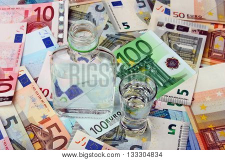 Bottle and a glass of vodka on a background euro money