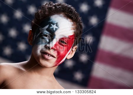 Adorable, mixed race boy, wearing red, white and blue face paint.  Blurred out American flag in the background.
