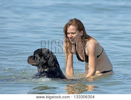 woman and rottweiler playing in the sea