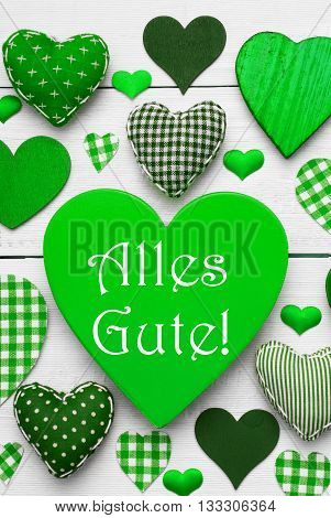 Green Vertical Heart Texture With German Text Alles Gute Means Best Wishes. White Wooden Background. Textile Hearts Which Are Dotted and Striped. Greeting Card For Birthday Wishes