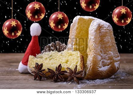 pandoro cake on wood with christmas balls, snowflake, cap of santa, star anise and pinecone