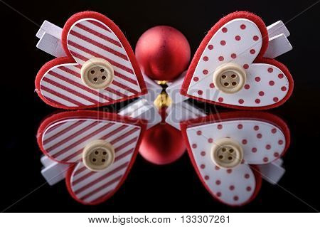 red christmas ball and heart clothespins reflected in a mirror with black background