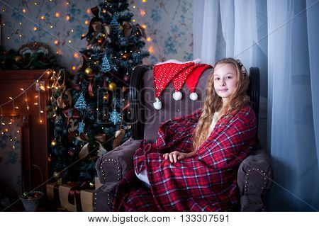 girl sitting in a chair wrapped in a blanket in the background of fireplace and Christmas tree