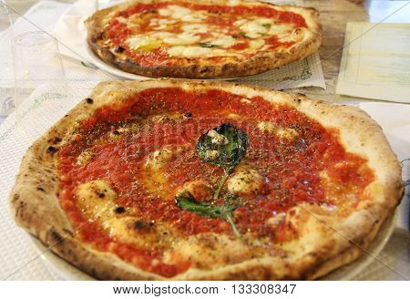Real Italian Pizza Margherita with tomatoes cheese and basil. Naples Italy.