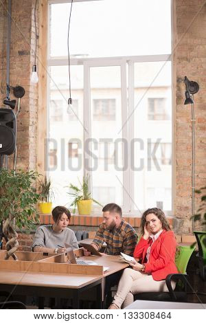 Closeup of beautiful and corporte business lady in red jacket looking at camera while her colleagues communicating about work in office.