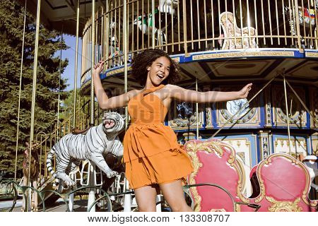 cool real modern teenage girl with candy near carousels at amusement park walking, having fun