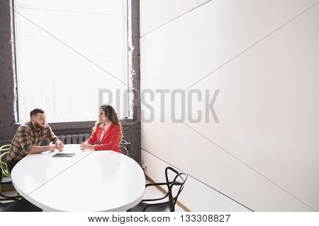 Picture of business meeting of man and woman in office. Man and woman communicating about business issues in bord room.