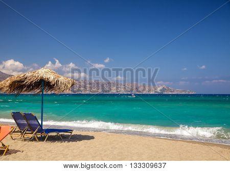 Blue sun loungers with parasol on a beach near Heraklion, Crete