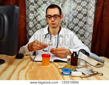 Male doctor holding thermometer with stethoscope in doctor's office