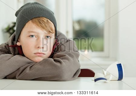 Teen Boy Leaning On Kitchen Table With Broken Mug