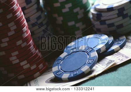 close-up casino chips and dollar bills on the poker table