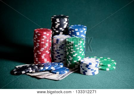 casino chips and dollar bills on the poker table