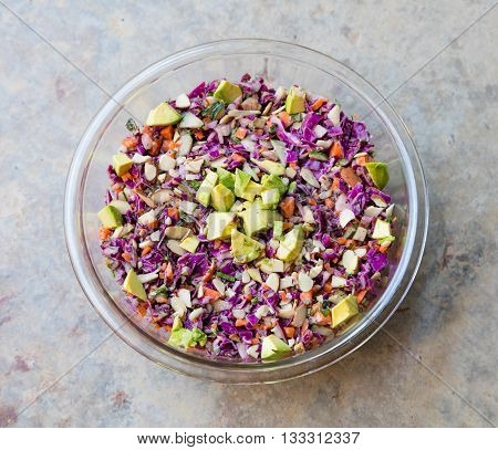 Top view of rainbow slaw with Avocado in a bowl