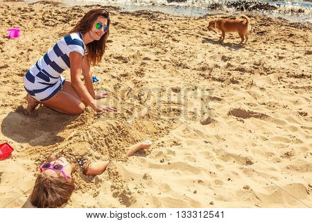 Mother And Daughter Playing On Beach.