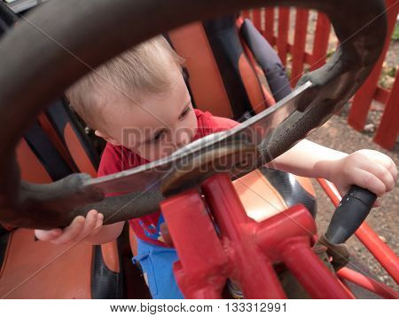 Little boy sitting behind the wheel of an immobile car truck in a playground