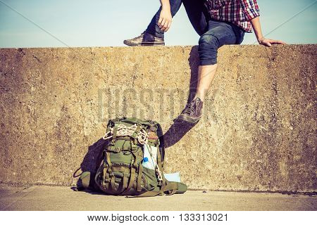 Man tourist backpacker relaxing outdoor sitting on grunge wall. Adventure summer tourism active lifestyle. Young guy tramping