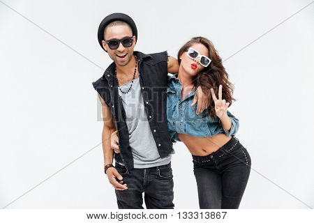 Cheerful playful young couple hugging and showing peace sign over white background
