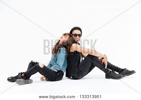 Beautiful young couple sitting back to back and smiling over white background
