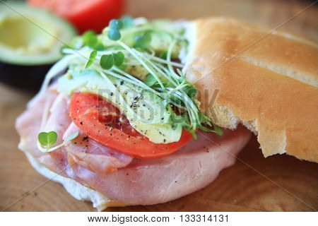 Sandwich of ham tomato avocado and sprouts with black pepper