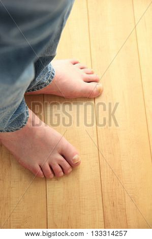 Man in jeans with bare feet on floor with copy space