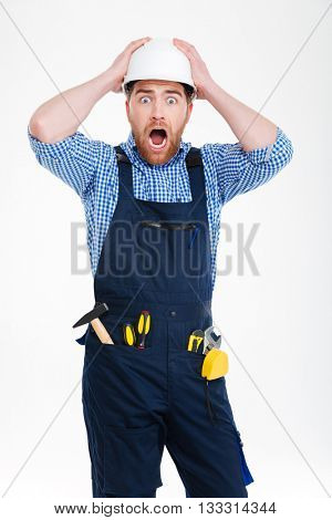 Astonished shocked young builder in helmet staning with mouth opened
