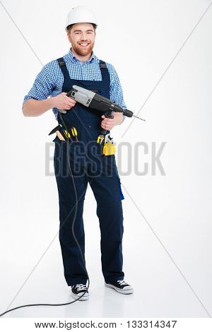 Cheerful handsome young builder in helmet standing and holding drill