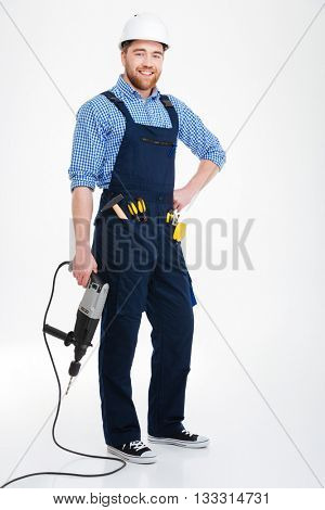 Full length of smiling attrative young builder in overall with drill