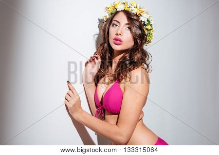 Close-up portrait of a sexy young attractive girl wearing flower diadem isolated on the white background