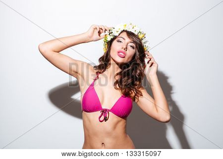 Portrait of a pretty girl wearing flower diadem in bikini isolated on the white background