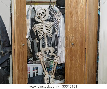 funny joyful skeleton sitting in the wardrobe-closet, wearing a white hat-- Everyone has a skeleton in their closets