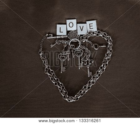 chain shaped as Valentine heart with various keys and love ward above on dark brown background