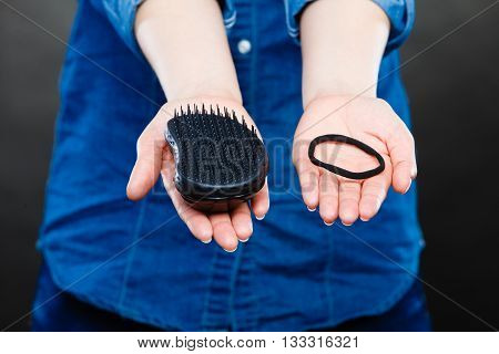 Female Hands With Comb And Elastic Hair.