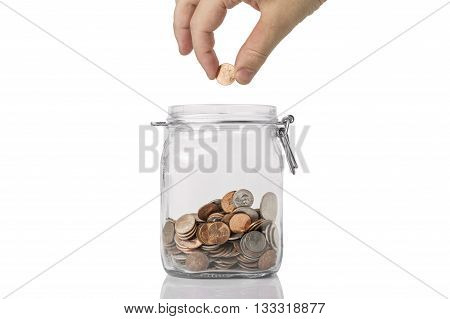 Penny Pinching or saving concept - a jar of American coins with a hand about to drop a penny into it.