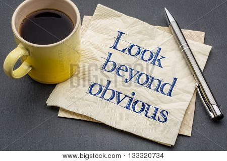 look beyond obvious - creativity and motivation reminder - handwriting on a napkin with a cup of coffee