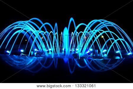 Close detailed view of dancing fountain at night blue lighting decoration