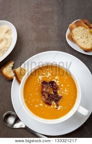 Butternut pumpkin soup, with crispy pancetta, parmesan and garlic bread.  Top view, over slate.