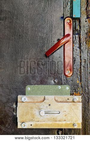 Fragment of an old wooden black door with a lock and a red handle