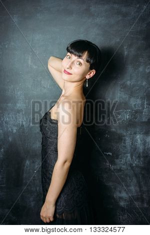 Beautiful young model woman in black dress posing over black slate background
